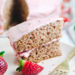 Slice of strawberry cake on a pink plate with a gold fork next to it and strawberries in the foreground