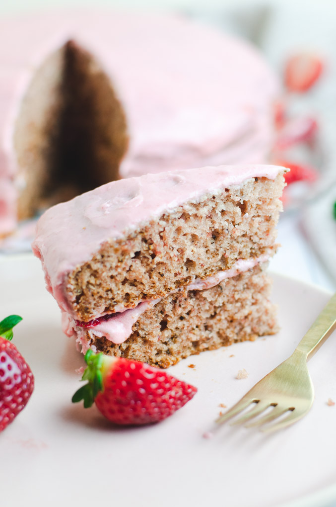 Slice Of Strawberry Cake On A Pink Plate With Gold Fork Next To It And