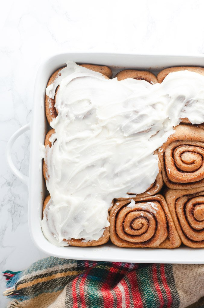 Vegan cinnamon rolls partially frosted with vegan buttercream