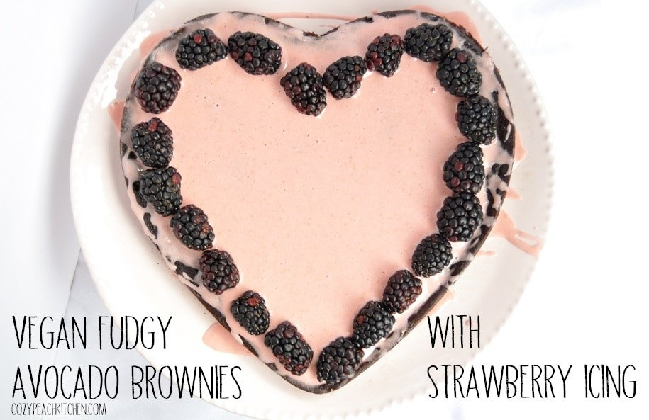 """Pink heart shaped cake topped with blackberries and labeled with """"vegan fudgy avocado brownies with strawberry icing"""""""