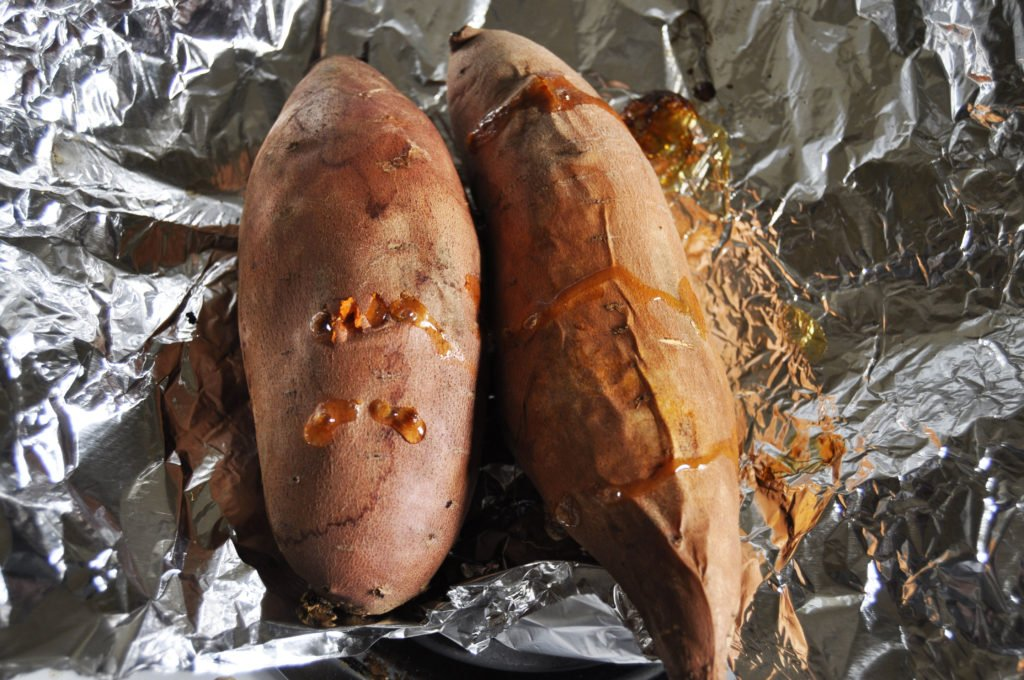Two roasted sweet potatoes on foil