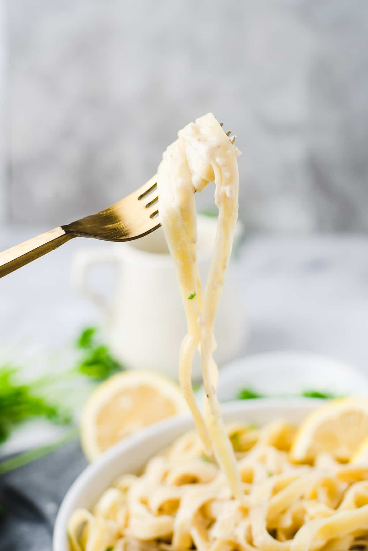 Forkful of fettucine being lifted out of a bowl filled with alfredo pasta