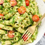Pasta with pesto and tomatoes and a gold fork