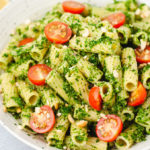 White bowl of pasta in pesto with cherry tomatoes