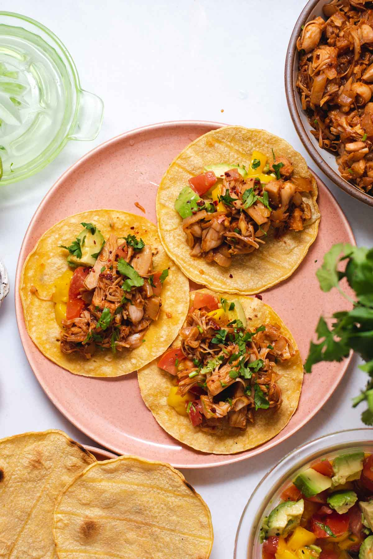 Overhead view of pink plate with three jackfruit tacos