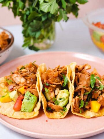 Side view of three corn tortillas filled with jackfruit, avocado and mango