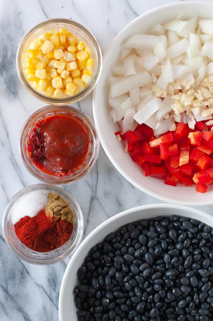 Ingredients to make black bean soup on a marble background