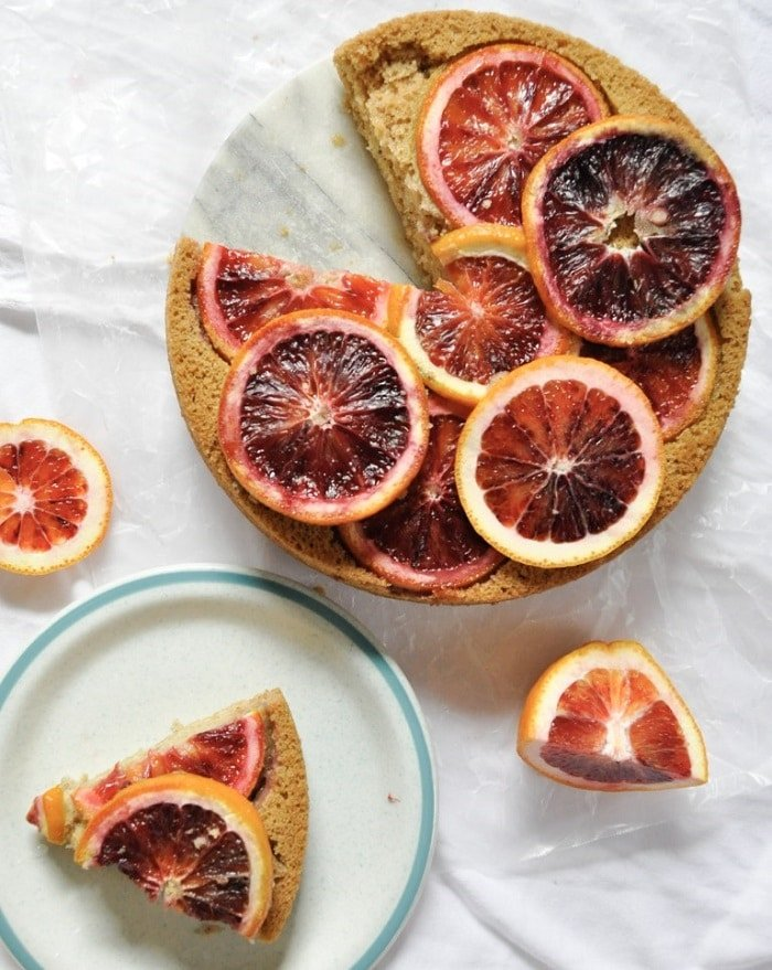 Cake topped with blood oranges next to slice of cake on white and blue plate