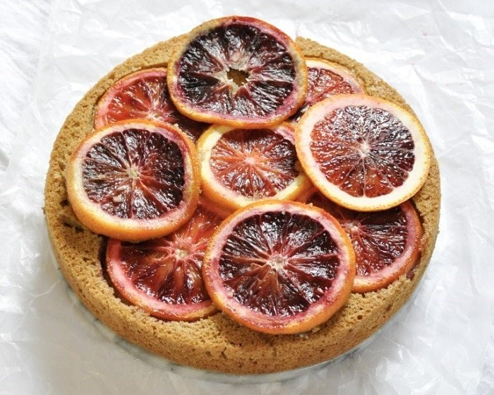 Close up of cake topped with blood oranges