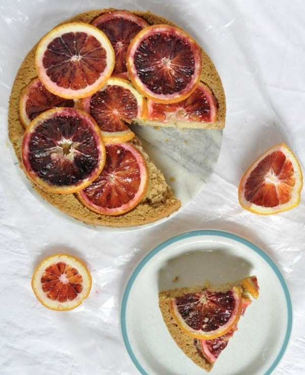 Cake topped with blood oranges on white background