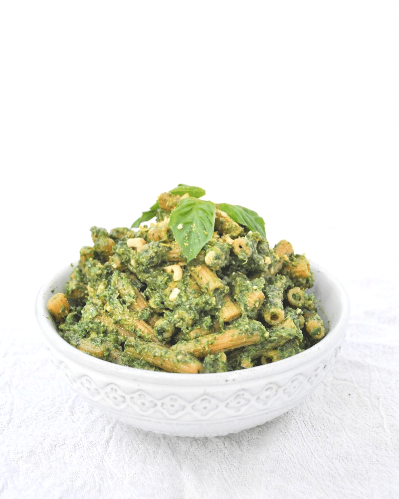 Creamy Vegan Avocado Pesto on pasta and topped with basil and cashew parmesan