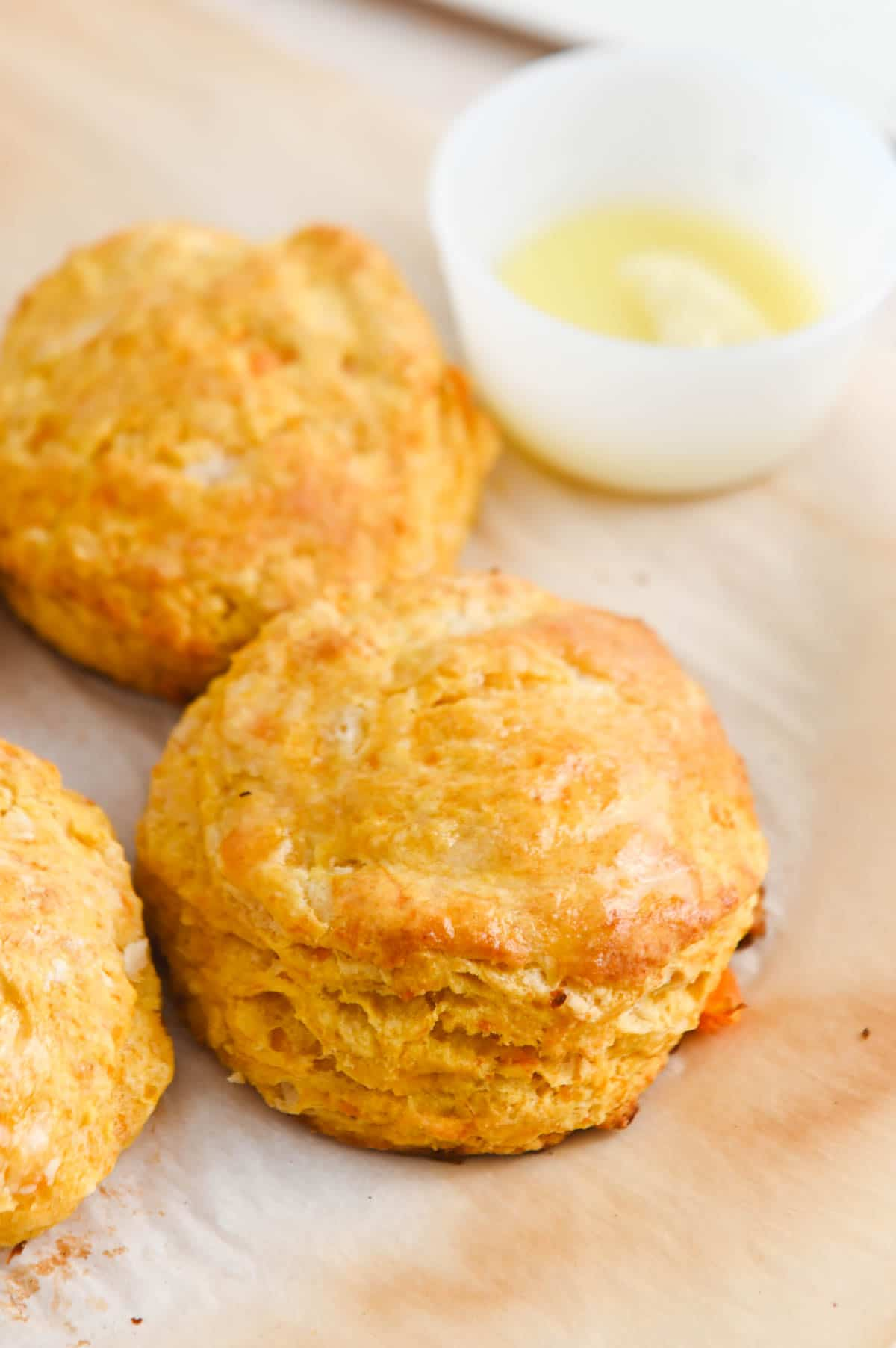 Sweet potato biscuit on parchment paper with another biscuit and white bowl in the background