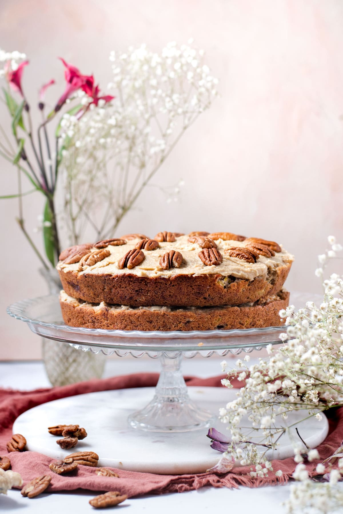Hummingbird cake on a glass cake stand surrounded by small white flowers