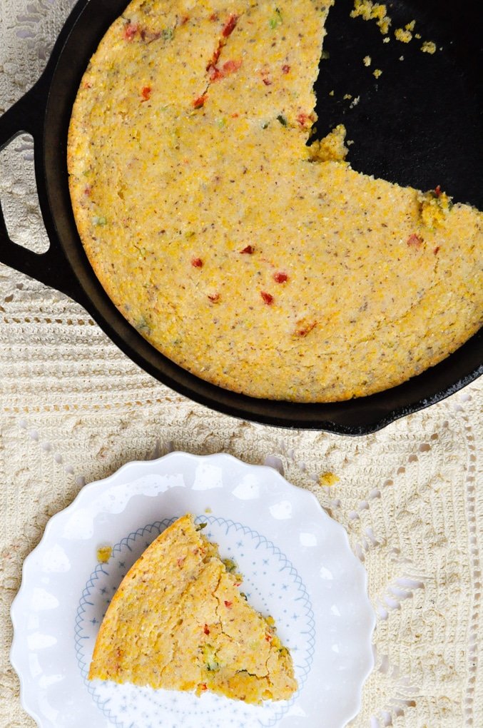 Cornbread on white plate next to cast iron filled with cornbread