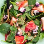 Close up of strawberries and goat cheese on spinach
