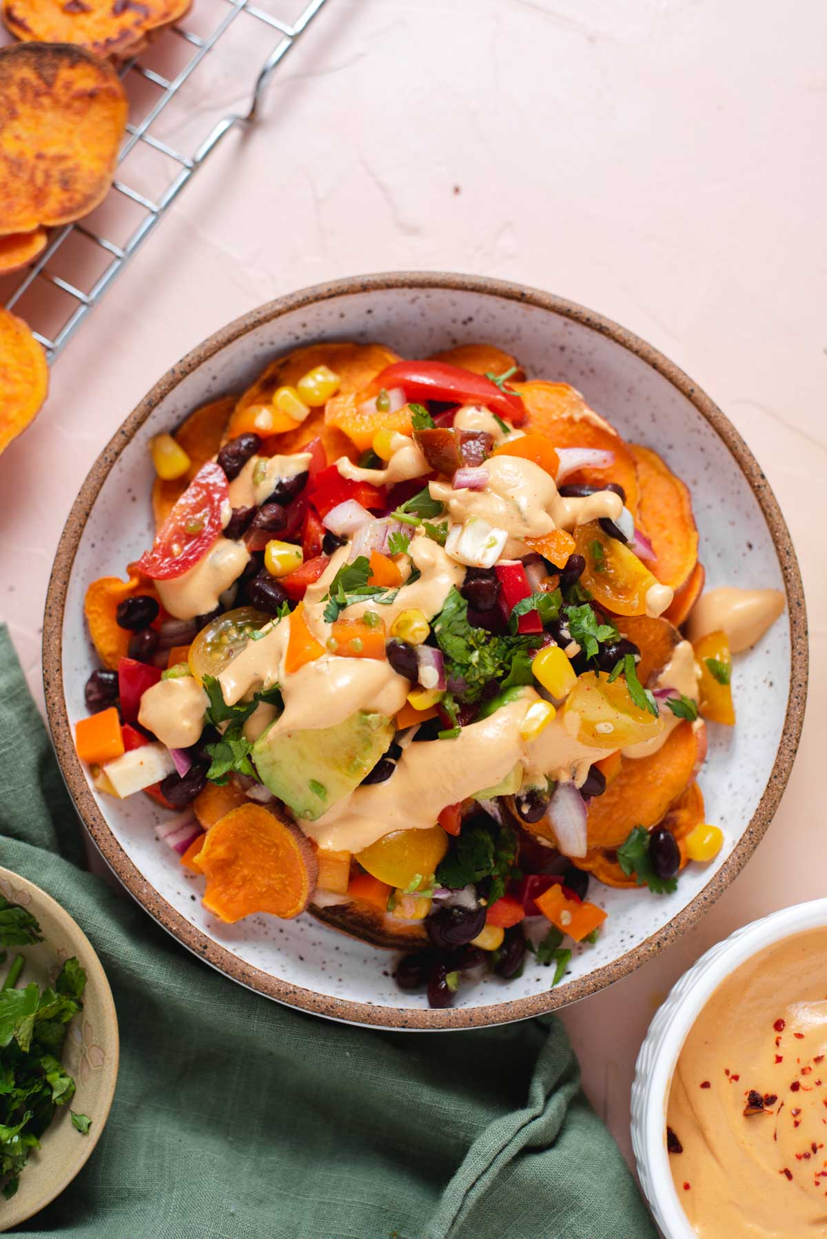 Overhead view of bowl of sweet potato nachos on a pink background