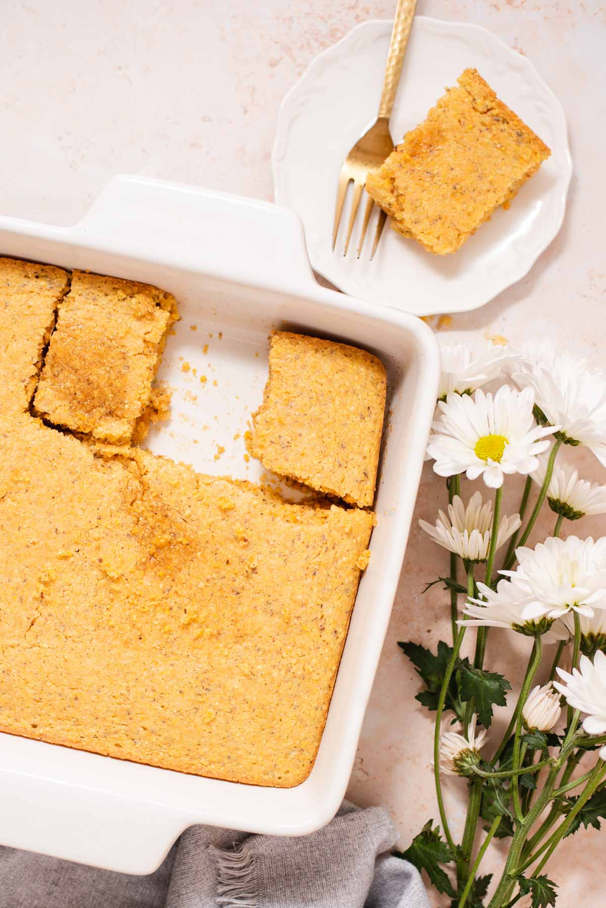 Overhead view of white ceramic dish filled with cornbread next to plate with slice of cornbread
