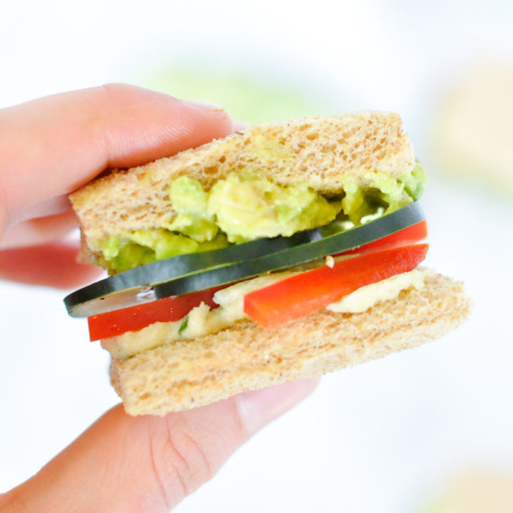 Fingers holding small cucumber sandwich