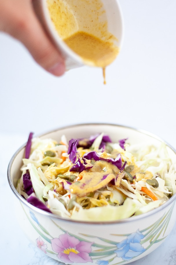 Coleslaw with spicy mustard sauce being poured onto it