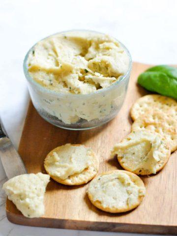 Cream cheese in glass jar on wood cutting board