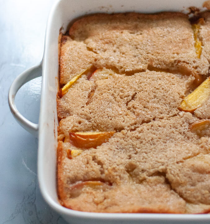 Peach cobbler in white baking dish