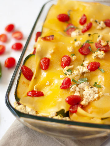 Close up of lasagna topped with cherry tomatoes and tofu ricotta