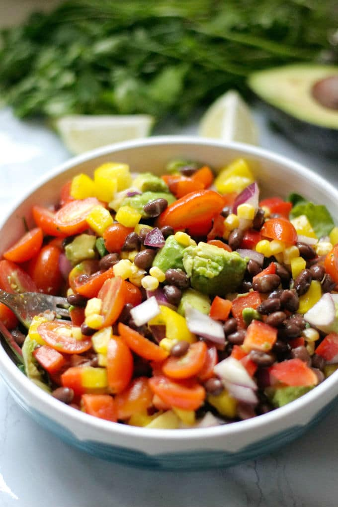 White and blue bowl filled with black bean salad