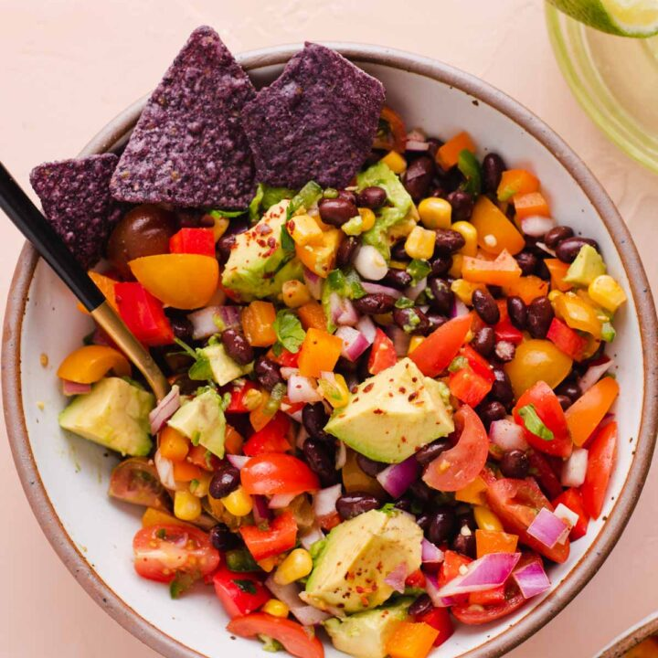 Overhead view of white bowl filled with black bean and corn salad with purple corn chips