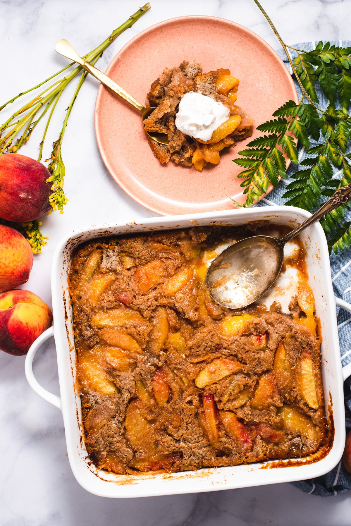 Square white casserole dish of peach cobbler next to pink plate with serving of cobbler
