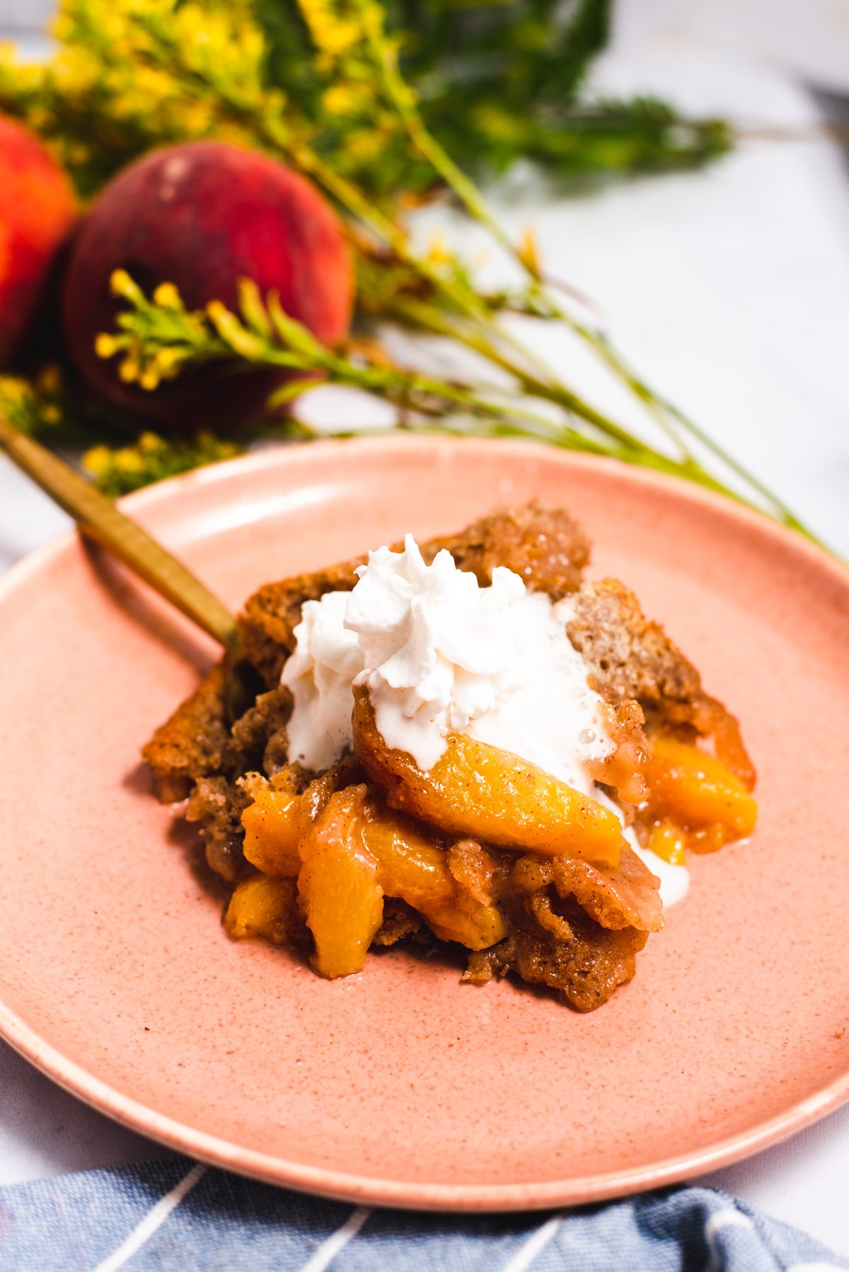 Serving of peach cobbler topped with whipped cream on a pink plate