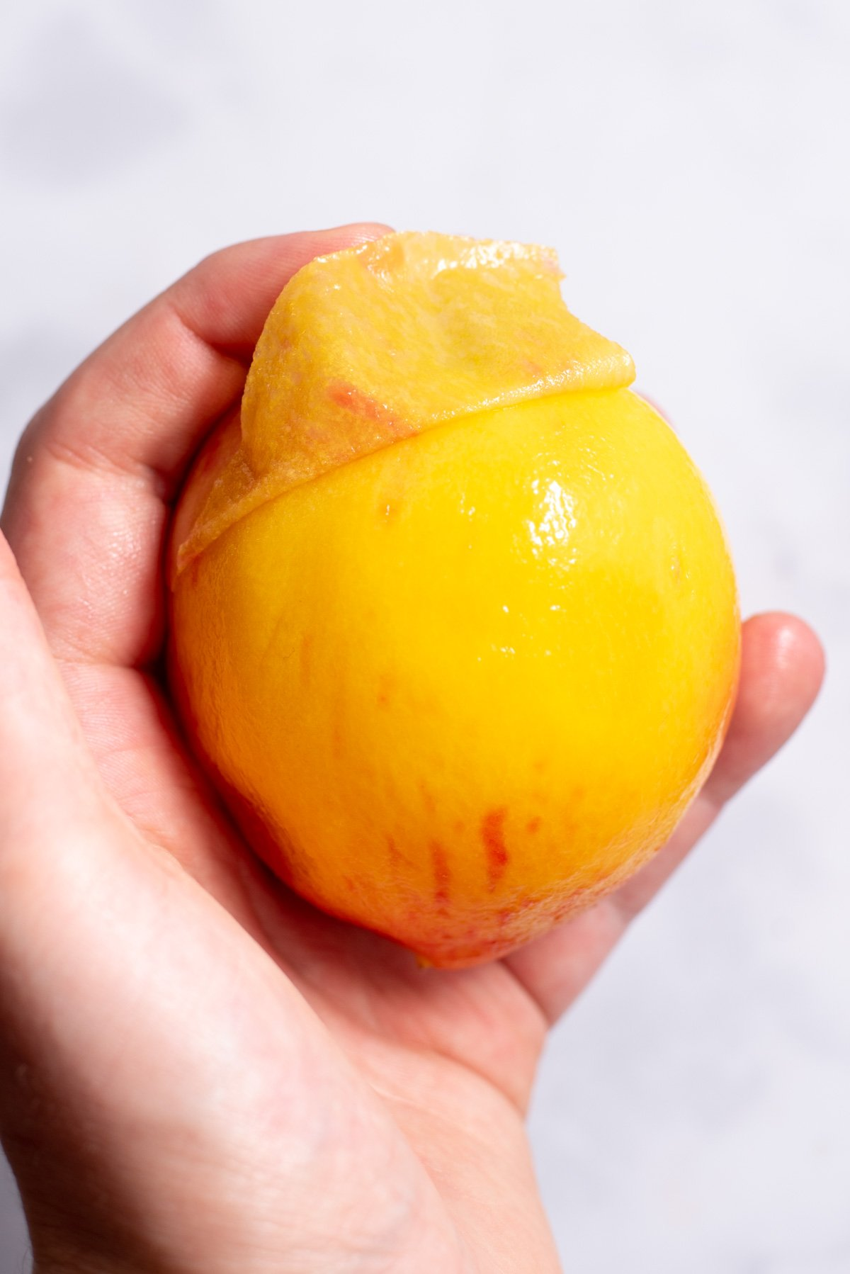 Peach with peeled skin in hand