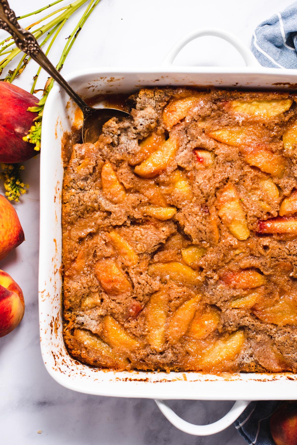 Close up of peach cobbler in white casserole dish