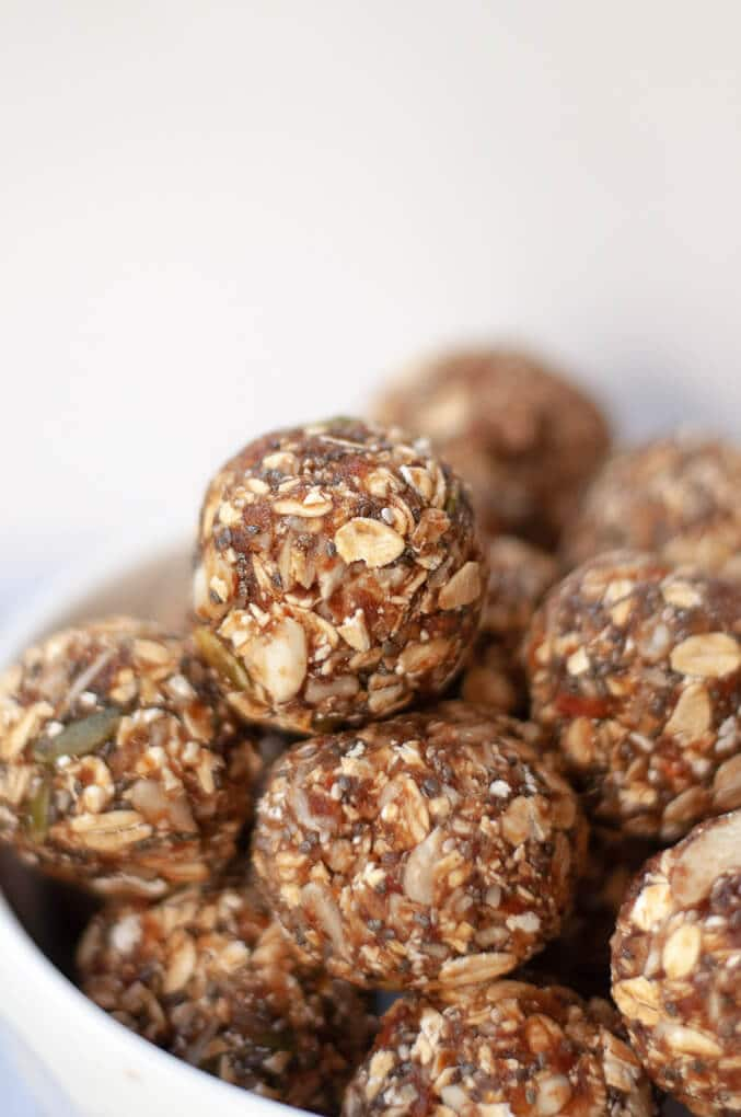 Bowl of no trail mix energy balls made with oatmeal, dates, nuts and seeds