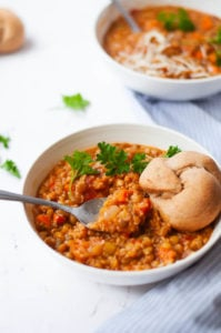 Lentil quinoa soup with spoon and garlic knot in a white bowl