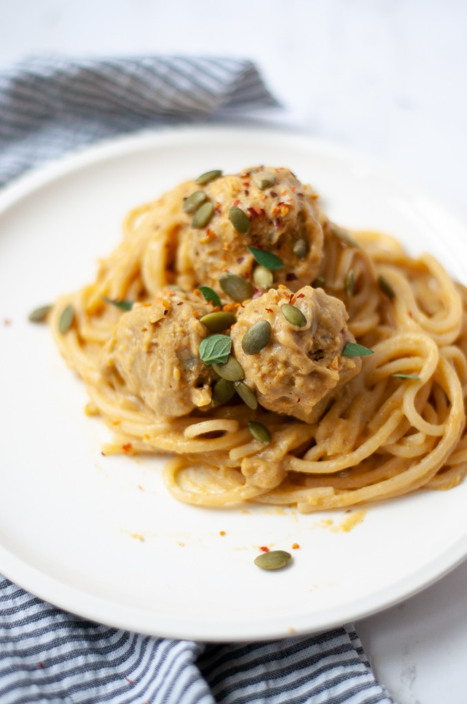 Close up of pasta with meatballs on a white plate