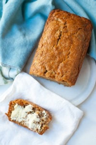 Slice of vegan zucchini bread and loaf of zucchini bread from above