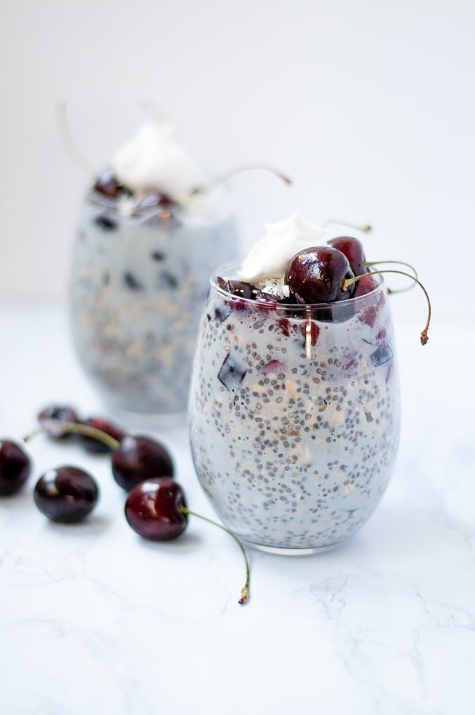 Cherry overnight oats with coconut cream and cherries on top