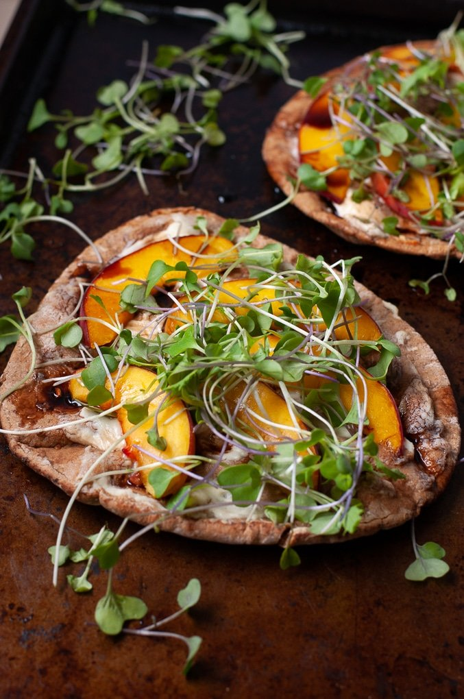 Close up of peach and goat cheese pita pizza topped with microgreens