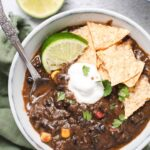 Close up of black bean soup in a gray bowl topped with cilantro, sour cream and a lime wedge