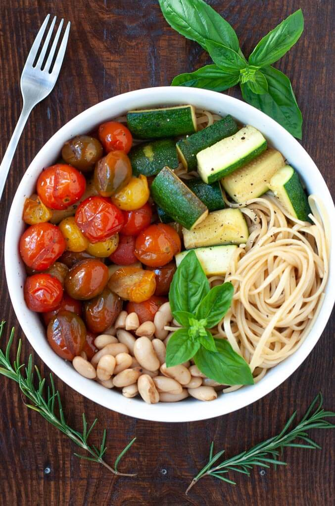 Cherry tomatoes, zucchini, cannellini beans in a bowl with linguine and basil