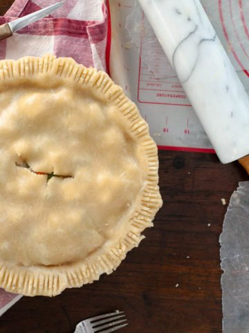 View of an uncooked pie from above with rolling pin