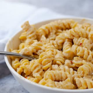 Close up of white bowl filled with vegan macaroni and cheese