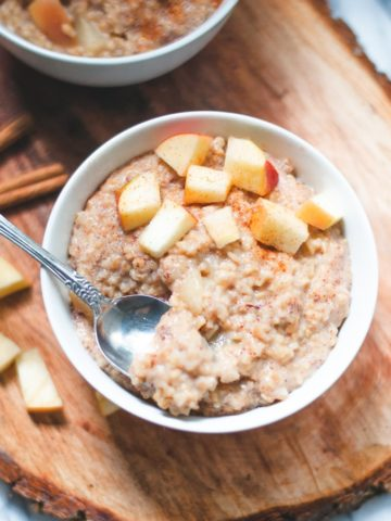 Bowl of apple cinnamon steel cut oats with spoon and apples