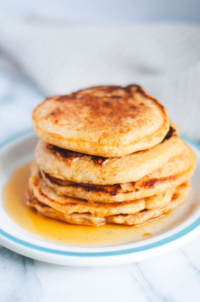Stack of vegan sweet potato pancakes covered in maple syrup