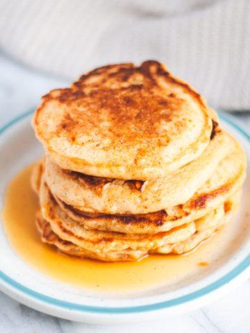 Stack of vegan sweet potato pancakes with syrup