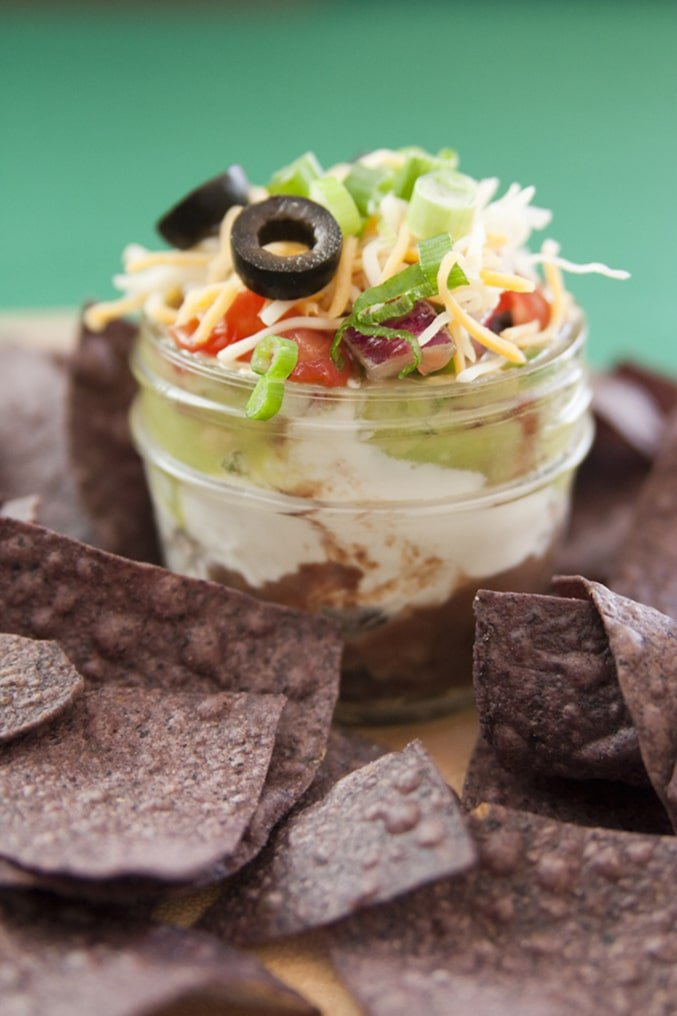 Seven layer dip in small white jar surrounded by blue chips