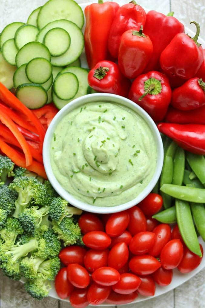 Green dip surrounded by vegetables