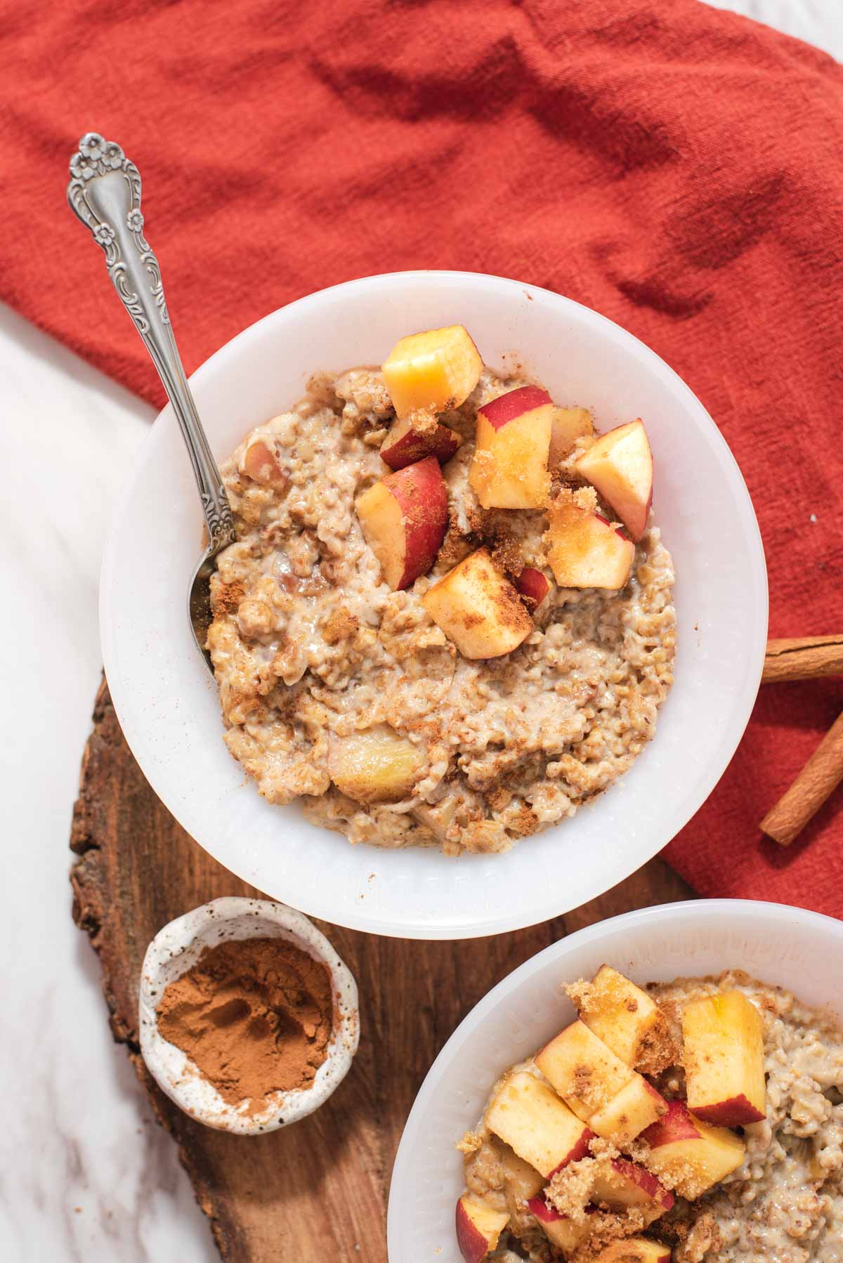 Overhead view of white bowl filled with oatmeal and diced apples