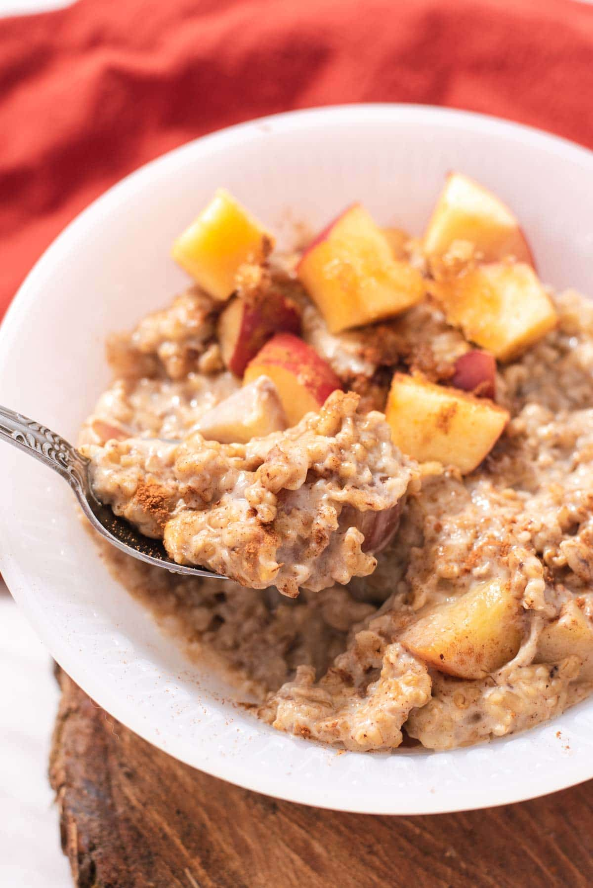 Silver spoon lifting a bite of steel cut oats out of a white bowl