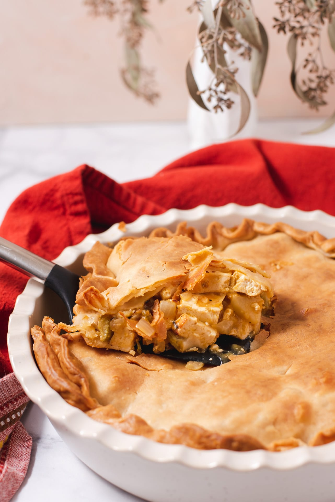 Slice of pot pie being lifting out of a pie dish